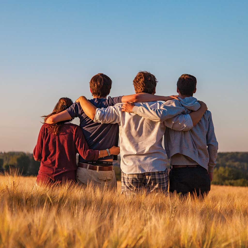 Picture of four friends in a field looking away from the camera with their arms over each others shoulders. Photo by Dimitri Houtteman,