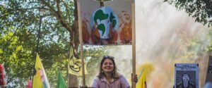 Photo of a young woman, holding a sign showing the earth on fire, at a climate demonstration. Credit Gabriel Mccallin.