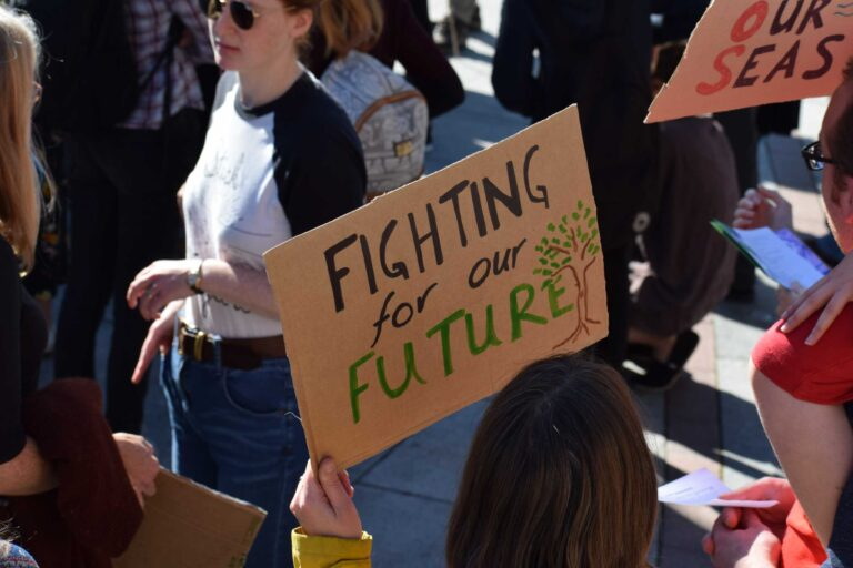 """Photo of a climate march, with a sign that says """"fighting for our future."""" Credit Ma Ti."""