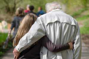 A photo of a young woman and old man, from behind, with their arms around each other. Credit Jana Sabeth.