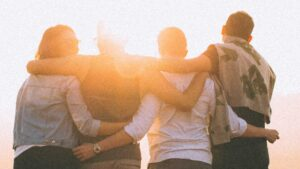 Photo of four youth, arms around each other, looking towards a sunrise. Credit Helena Lopes.