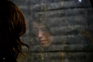 A photo of a young woman's reflection in a window. Photo by Tiago Bandeira.