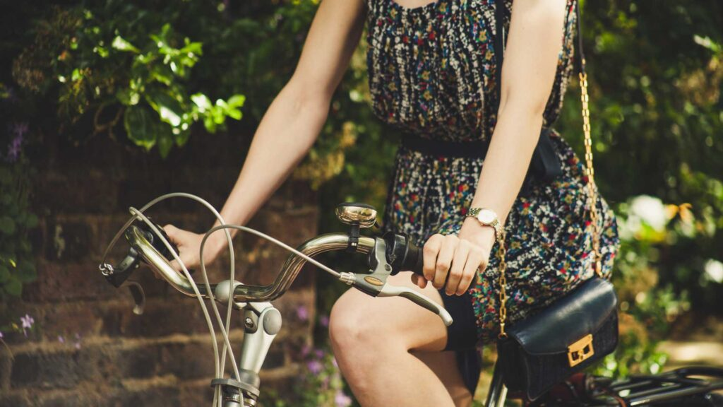 Photo of a woman on a bicycle. The photo crops out the woman's head and feet. The woman is wearing a dress. Credit blubel.